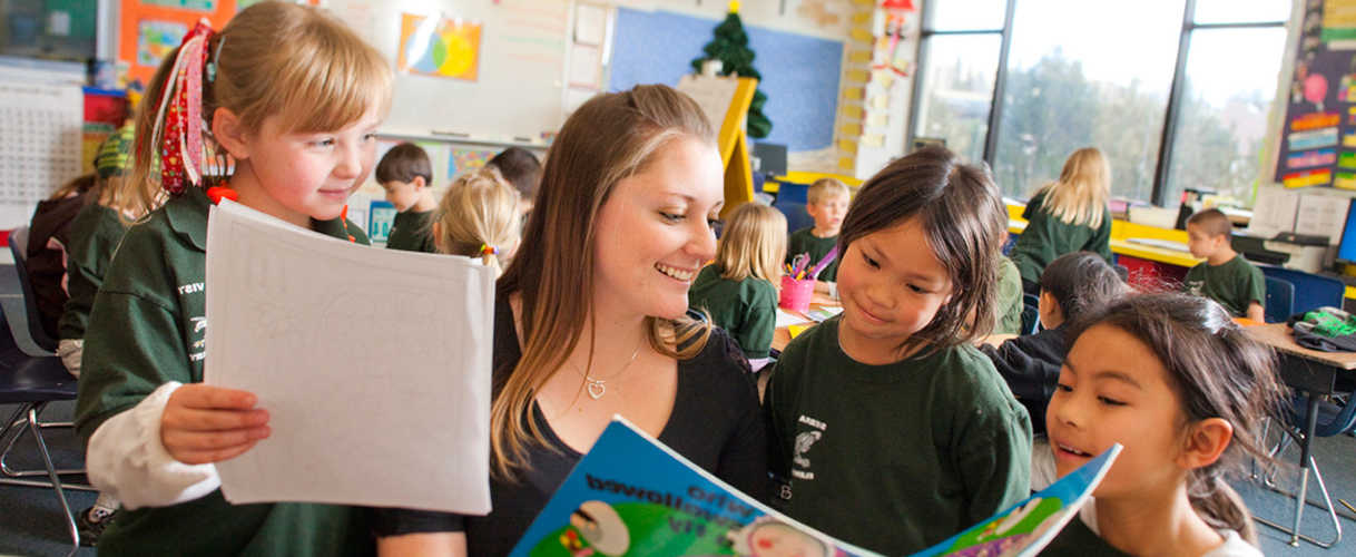 Teacher shares a book with three elementary school students